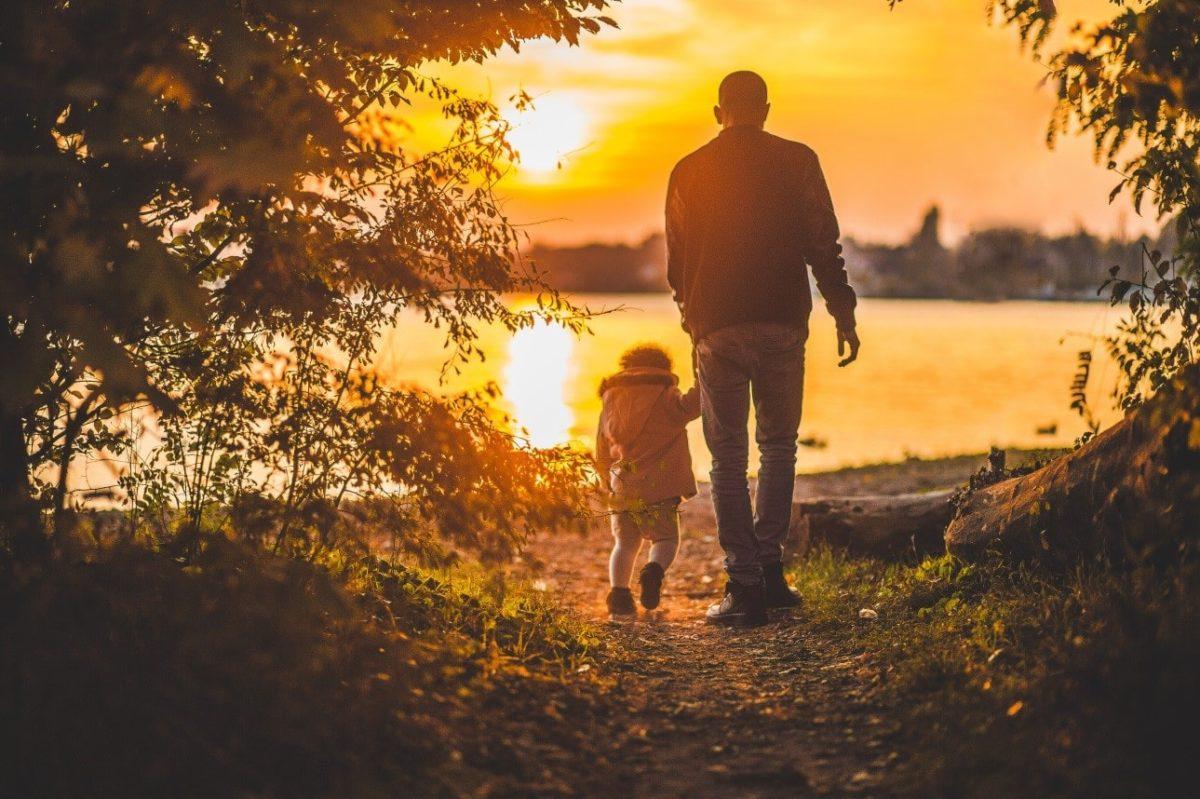 man and child walking toward water sunset