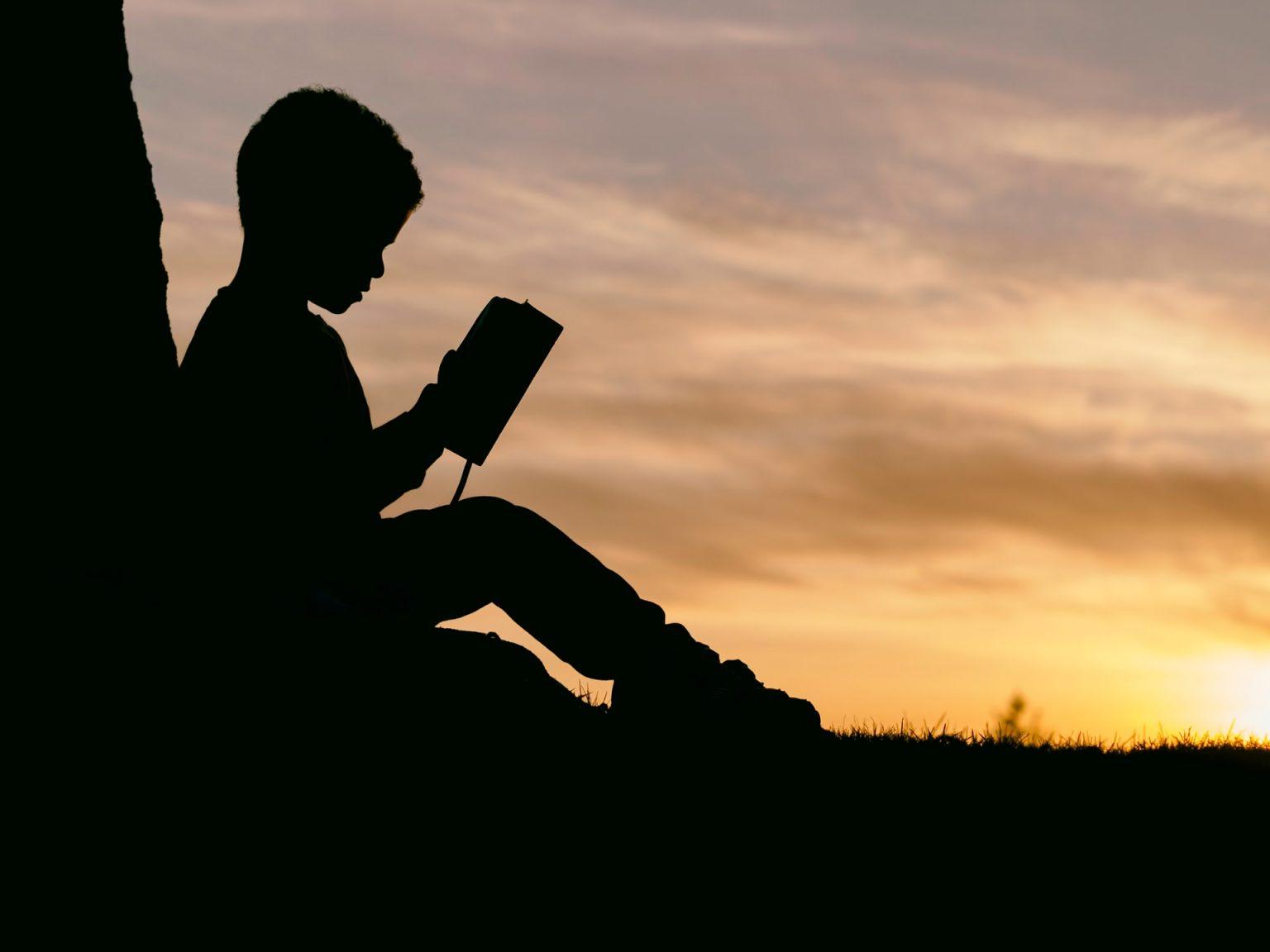 child reading Bible sunset